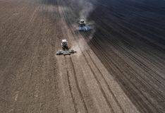 Two bright blue tractor plowing the ground against a black earth background. Stock Photo