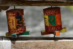 Two bright Buddhist prayer drums in mountain village, painted Sanskrit mantras with metal paints, Ladakh, Northern India. Royalty Free Stock Photography