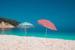 Two bright colored sun beach umbrella on pebble beach against turquoise blue sea water surface and clean blue sky.  Stock Photos