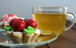Bright cakes in the form of baskets on the background of a dark wooden table with tea. Two bright cream cakes in the form of baskets on the background of a dark Royalty Free Stock Photos