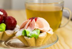 Bright cakes in the form of baskets on the background of a wooden table with tea. Two bright cream cakes in the form of baskets on the background of a wooden Royalty Free Stock Image