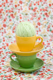Two bright cups and a ball of yarn on a background Royalty Free Stock Photos