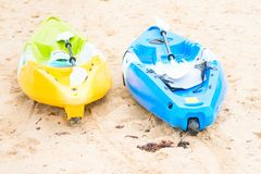 Two bright empty canoe at sand beach. Two bright empty yellow and blue canoe at sand beach Stock Image