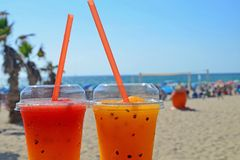 Two bright fruit cocktails with ice in glasses with tubes. Cool drinks on the beach against the backdrop of palm trees and sea stock photos