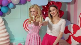Two bright girls in pink dresses with champagne. Two bright happy girls in pink dresses with champagne in hands clink on camera against the background of huge stock video