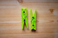 Two bright green clothespins on the wooden table stock image