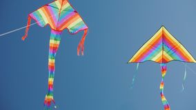 Two bright kite flying high in the sky, soaring in the sky nearby