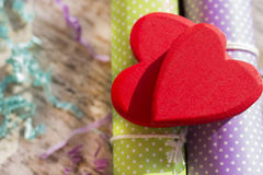 Two bright red hearts on wrapping paper. Blurred background. Postcard or background on Valentine`s Day Stock Photo