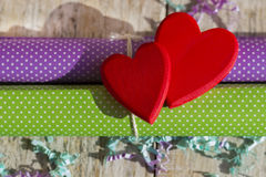 Two bright red hearts on wrapping paper. Postcard or background on Valentine`s Day Royalty Free Stock Photo