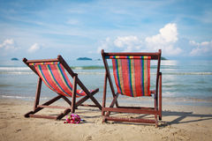 Two bright sun loungers on the beach. Stock Photos