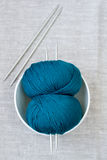 Two bright turquoise skeins of thread and needles Stock Photos