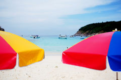 Two bright umbrellas on tropical beach. Bright umbrellas on a beach Royalty Free Stock Images
