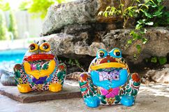 Two brightly colored and decorated ceramic frogs sit by landscaping rocks by swimming pool royalty free stock photography