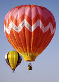 Two Brightly Colored Hot Air Balloons. A pind and red zig zag striped hot air balloon soars through the air with another yellow balloon in the distance Stock Photo