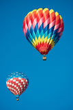 Two brightly colored hot air balloons with a sky blue background Royalty Free Stock Photography