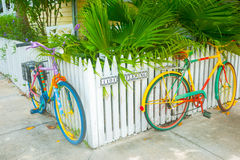 Two brightly painted bicycles leaning on picket fence on residen Royalty Free Stock Photos