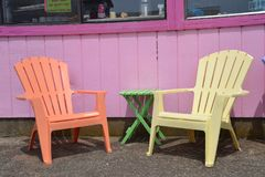 Outdoor Seating for Cafe in Taft/Lincoln City, Oregon. Two brightly painted chairs with a small table in front of a cafe`s pink wall in Taft/Lincoln City, Oregon royalty free stock photo