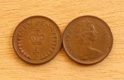 Half Pennies. Two British Decimal Halfpenny Coins on a Wooden Background. Front and Back Views royalty free stock photography