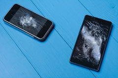 Two broken mobile phones on painted wooden table. Background royalty free stock images
