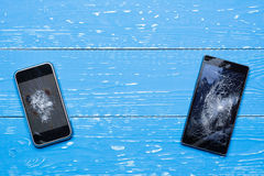 Two broken mobile phones on vintage painted table. Two broken mobile phones on vintage painted wooden table royalty free stock photos