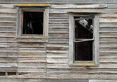 Two Broken Windows in a Dilapidated Wooden House Royalty Free Stock Photos