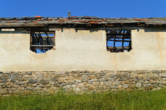 Two broken windows of ruined cottage Stock Photo