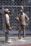 Two bronze sculptures in front of a metal grate in Cologne in Germany Stock Image