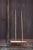 Two brooms in front of an old barn Royalty Free Stock Photos