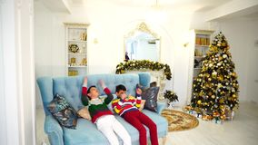 Two of brother`s children do not want to fulfill their parents` orders and show discontent sitting on blue sofa in stock video footage