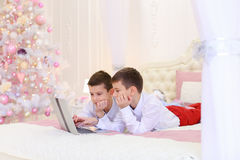 Two of brother`s children play computer games and lie on bed in Stock Photos
