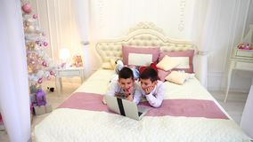 Two of brother`s children play computer games and lie on bed in bright room with Christmas tree in daytime. Boys, siblings together look at laptop screen and stock video footage