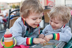 Two brother toddler boys playing with tablet pc Royalty Free Stock Photo