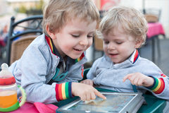 Two brother toddler boys playing with tablet pc Royalty Free Stock Photography