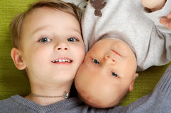 Two brothers. Three years old blond caucasian boy lying on a sofa with his few weeks old brother Stock Photos