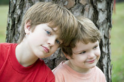 Two brothers. Sitting together by a tree stock photo