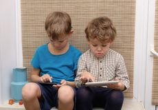 Two brothers, ages four and seven play games on smartphone and tablet. Two brothers of European appearance four and seven years old enjoys playing games on your Royalty Free Stock Photo