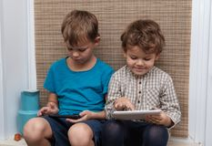 Two brothers, ages four and seven play games on smartphone and tablet. Two brothers of European appearance four and seven years old enjoys playing games on your Stock Photo