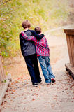 Two brothers hugging and walking on bridge Royalty Free Stock Images