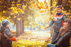 Two brothers in autumn park. Mother and suns play in the autumn park Stock Photos