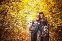 Two brothers in autumn park. Mother and suns walking in the autumn park Stock Photography