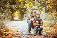 Two brothers in autumn park. Brothers walking with his four year old brother in the autumn park. Vertical view Royalty Free Stock Image