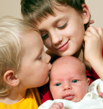 Two brothers and baby sister. Sweet tender moment of brothers and their 1 old month sister communicating Royalty Free Stock Photos