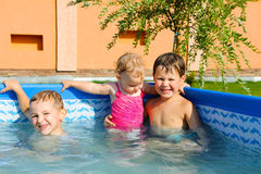 Two brothers and baby sister in the pool Stock Images