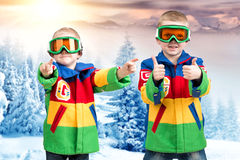 Two brothers of the boy snowboarder in bright ski jackets and goggles is skiing in the mountains. Boys snowboarder in bright ski jackets and goggles is skiing stock image