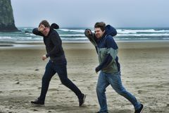 Two young men on a windy beach. Two brothers brave the windy cold wet weather at Cannon Beach on the Oregon Coast. They shield their faces with their arms and stock photography