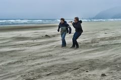 Two young men on a windy beach. Two brothers brave the windy cold wet weather at Cannon Beach on the Oregon Coast royalty free stock photo