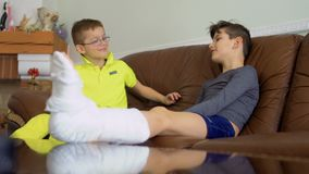 Two brothers with broken leg and hand sitting on sofa at home and talking. The boys are boring and suffers foolishness. Boys high-five with each other. Two stock video footage