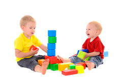 Two brothers build toy building of colored cubes Stock Photography