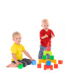 Two brothers build toy building of colored cubes Stock Images
