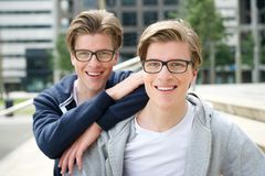 Two brothers. Close up portrait of two brothers with glasses smiling outdoors stock photos